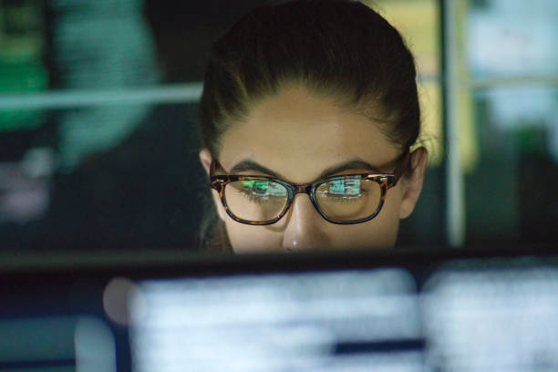 Close up stock photo of a young woman surrounded by monitors & their reflections displaying scrolling text & data.